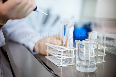Buy stock photo Researcher's hand holding a syringe over test tubes for an experiment in a laboratory