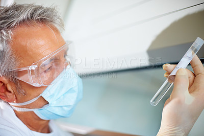 Buy stock photo Male researcher looking at a test tube containing a solution at the laboratory