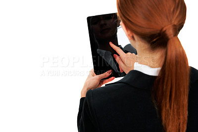 Buy stock photo Over the shoulder view of a young businesswoman browsing through her digital tablet