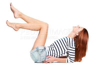 Buy stock photo Side-view of a young woman leaning back on her elbows with her legs in the air