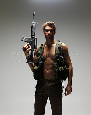 Buy stock photo Soldier with a bare chest holding up his M16 rifle while looking seriously at the camera - portrait