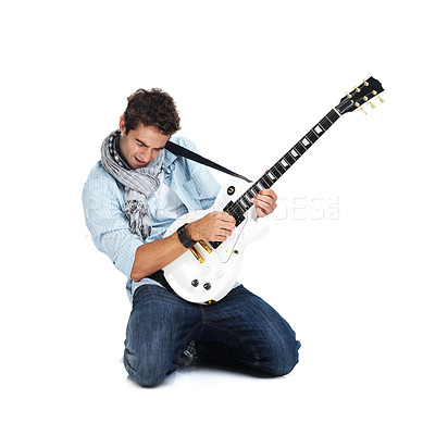 Buy stock photo Trendy male guitarist playing guitar while kneeling and tilting the instrument upwards