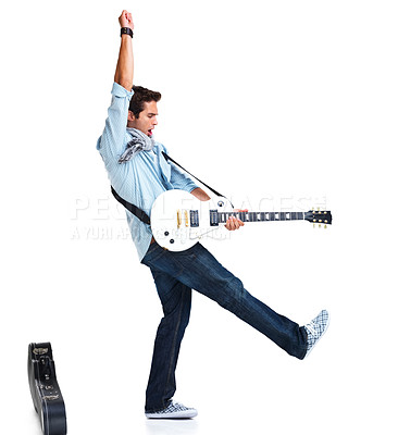 Buy stock photo Trendy young guitarist holding his guitar and posing with his one arm and leg in the air, with his guitar case lying next to him