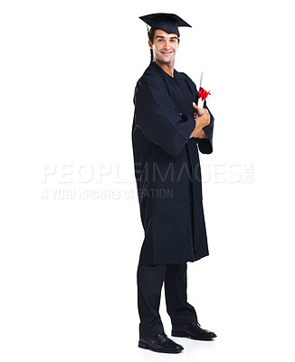 Buy stock photo Handsome young graduate wearing a black gown and cap smiling at the camera with his arms folded