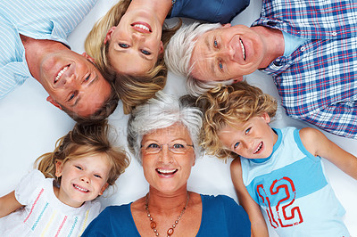 Buy stock photo Top view of happy multi generation family lying down and smiling at the camera