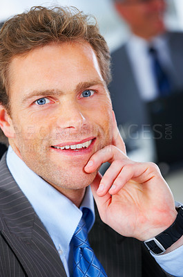 Buy stock photo Mature and attractive business man sitting in a office with colleagues in the background