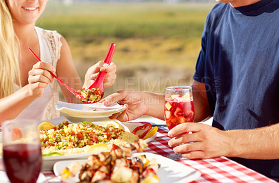 Buy stock photo Cropped image of a young couple eating a meal outside