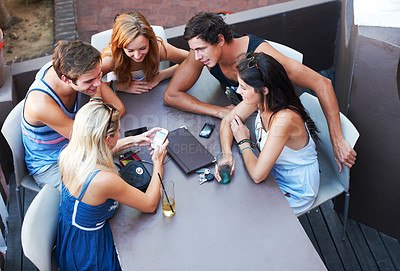 Buy stock photo Group of teens enjoying beverages while at an outdoor restaurant - high angle