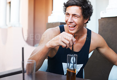 Buy stock photo Handsome young guy laughing while enjoying his cold beverage