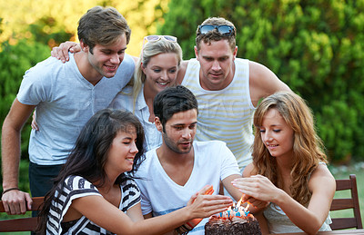 Buy stock photo Happy young teen friends celebrating someone's birthday with a cake and candles