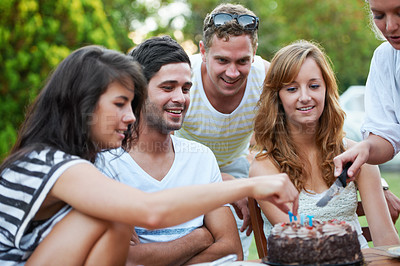 Buy stock photo Smiling young teen friends celebrating someone's birthday and cutting some birthday cake