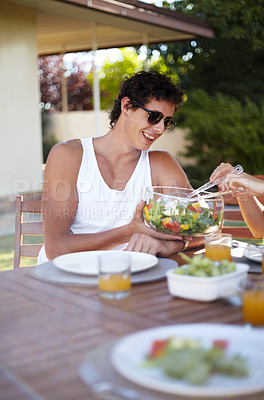 Buy stock photo Handsome young guy receiving a serving of salad at lunch