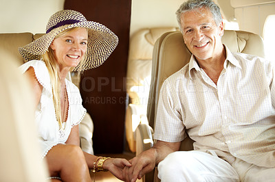 Buy stock photo Smiling senior couple holding hands on an airplane heading overseas - portrait