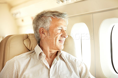 Buy stock photo Handsome senior man sitting in an airplane with a smile and looking out the window