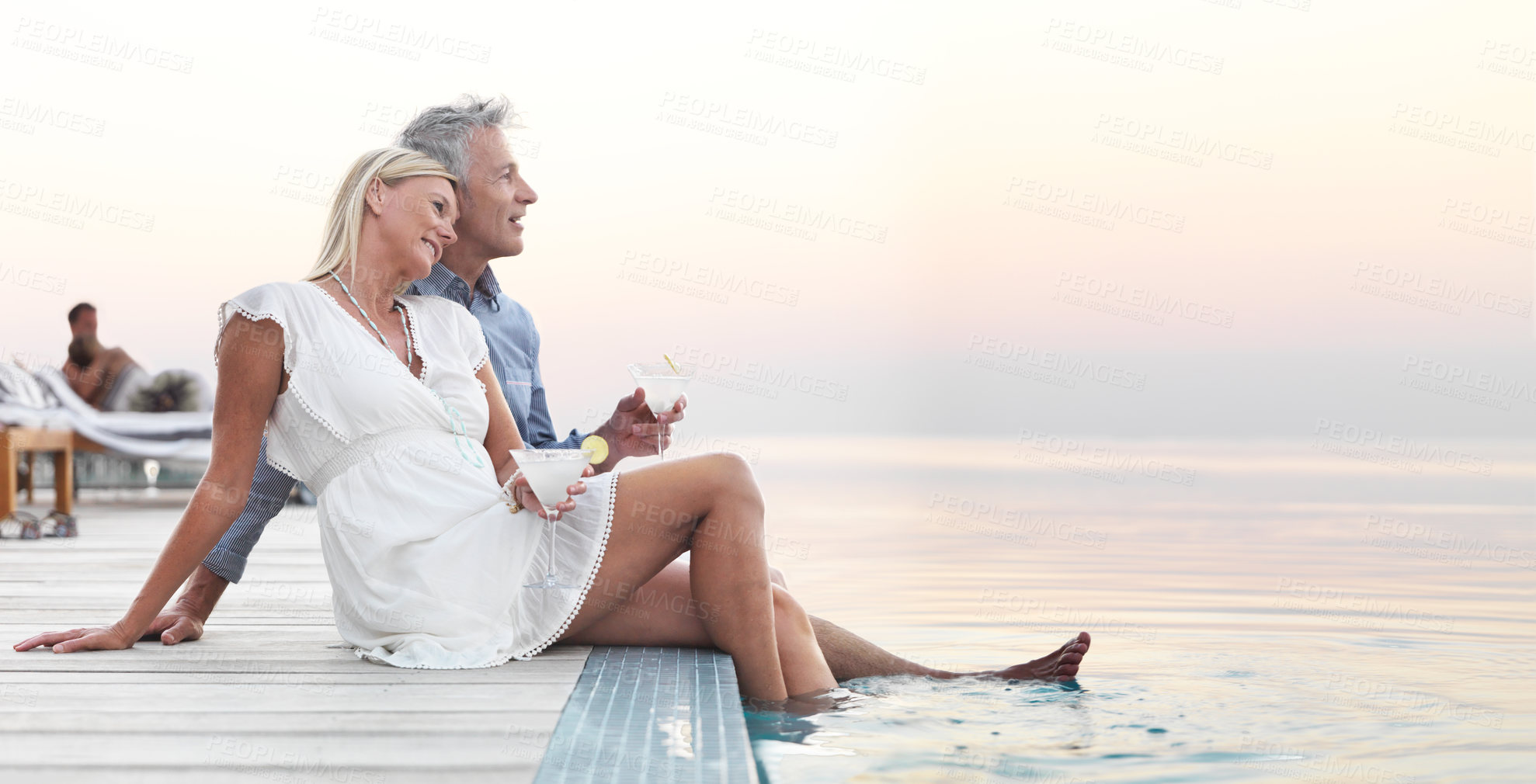 Buy stock photo Mature couple sitting on a deck enjoying some cocktails at dusk