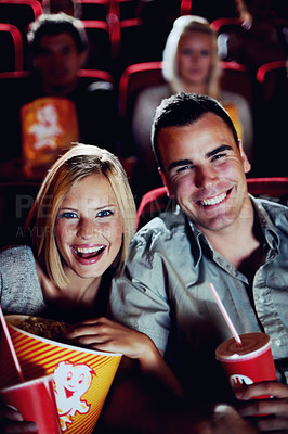 Buy stock photo Portrait of a happy couple sharing popcorn in a movie theatre