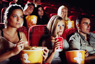 Buy stock photo Friends sitting with refreshments and popcorn enjoying a movie together