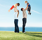 Happy parents carrying children on grass