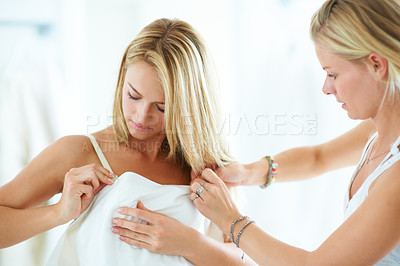 Buy stock photo A young bride with her friend choosing a wedding dress