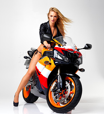Buy stock photo Studio portrait of a sexy young woman in a leather jacket and bikini riding a motorbike