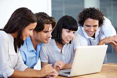 Buy stock photo A group of young entrepreneurs having a business meeting over a laptop