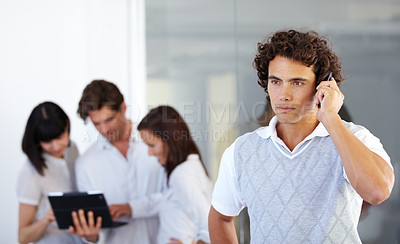 Buy stock photo An entrepreneur taking a cellphone call while colleagues have a discussion in the background