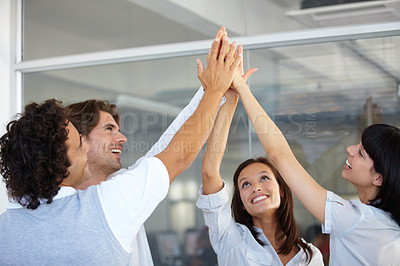 Buy stock photo Colleagues high-fiving one another after a deal has been closed