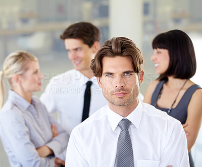 Buy stock photo Portrait of a handsome executive with his arms folded - blurred colleagues in the background
