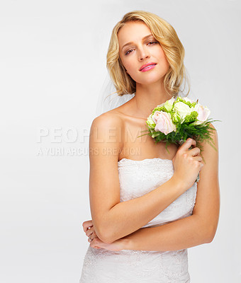 Buy stock photo Wistful young bride holding her bouquet