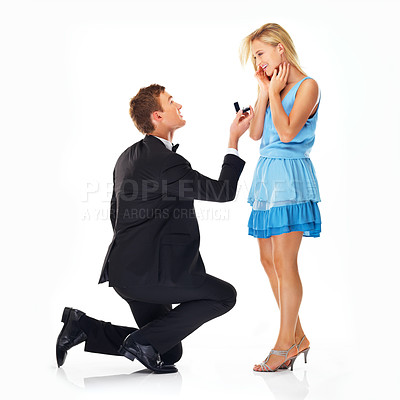Buy stock photo Handsome young man proposing to his surprised girlfriend