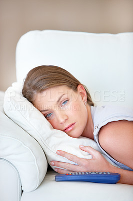 Buy stock photo Pretty young woman lying on the sofa with a TV remote and looking sad
