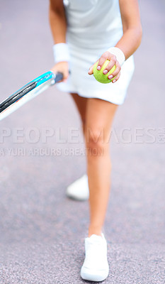 Buy stock photo Cropped view of a young female tennis player getting ready to serve the ball
