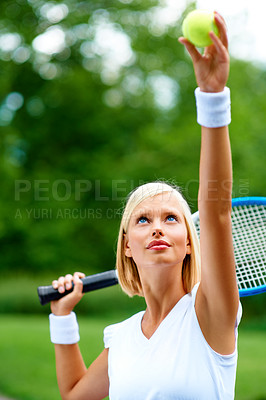 Buy stock photo A young female tennis player getting ready to serve the ball