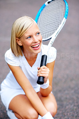 Buy stock photo A young tennis player kneeling down and daydreaming of winning her match