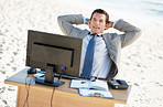 Relaxed middle aged business man at his office desk on a beach