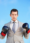 Serious middle aged executive wearing boxing gloves against sky