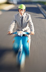 Blurred motion of a business manager riding a scooter