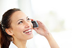 Pretty young woman enjoying a conversation on cellphone on white