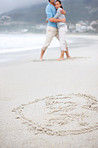 Love symbol on beach with a couple hugging in background