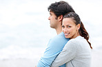 Smiling young female hugging her boyfriend fron behind at the be