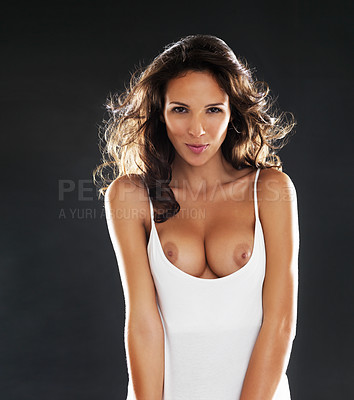 Buy stock photo Studio portrait of a sensual young woman wearing a white vest and showing her breasts while standing against a black background