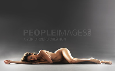 Buy stock photo Studio portrait of a gorgeous nude woman lying on the floor against a grey background