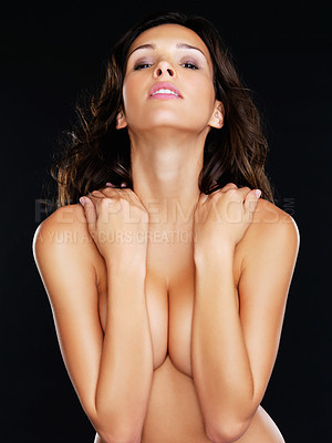 Buy stock photo Studio portrait of a seductive young topless woman covering her breasts while standing against a black background