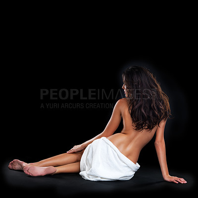 Buy stock photo Rearview studio shot of a beautiful young nude woman with a towel around her waist sitting against a black background