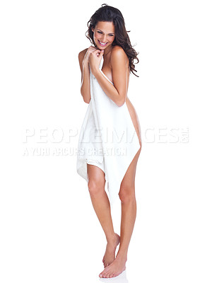 Buy stock photo Studio portrait of a beautiful young woman holding a towel to cover herself while standing against a white background