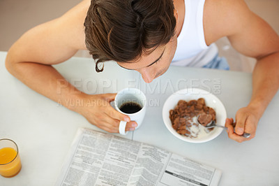 Buy stock photo High-angle view of a young man eating cereal while reading the daily newspaper