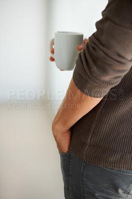 Buy stock photo Cropped image of a young man holding a cup of coffee