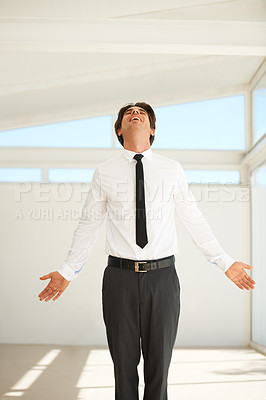 Buy stock photo A young businessman throwing his head back with joy