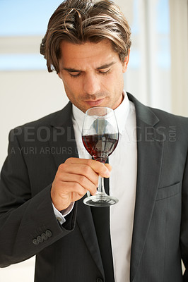 Buy stock photo A handsome wine connoisseur enjoying a glass of red wine