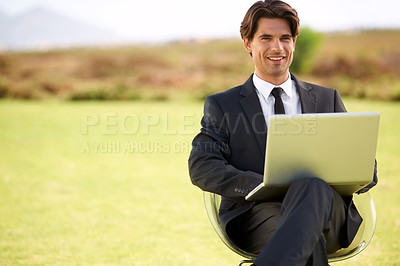 Buy stock photo Portrait of a young businessman sitting outside with his laptop